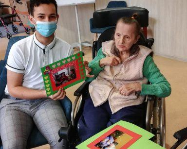 Referent Krzysztof Hadjas i seniorka prezentują wspólnie udekorowane zdjęcie. Ma ramkę z czerwonego i zielonego papieru z przyklejonymi serduszkami oraz motylkiem.