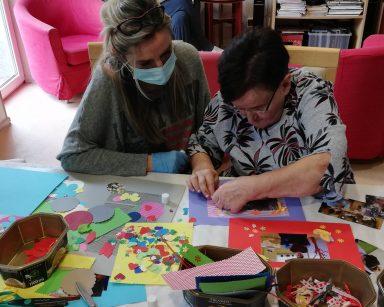 Specjalistka do kadr i płac Anna Foras-Misiewicz siedzi obok seniorki. Wspólnie dekorują zdjęcie. Przed nimi na blacie widać kolorowe papierowe ozdoby: motylki, serduszka, kwiatki, kokardki.