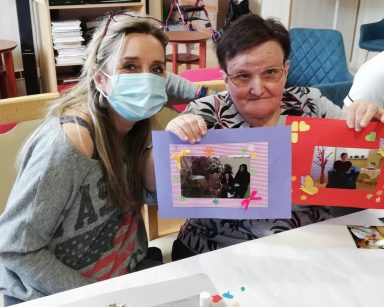 Specjalistka do kadr i płac Anna Foras-Misiewicz siedzi obok seniorki. Seniorka prezentuje swoje zdjęcia w papierowych ramkach. Pierwsze ma fioletową ramkę, drugie czerwoną ramkę z papierowymi ozdobami: motylkami, serduszkami i kwiatkami.