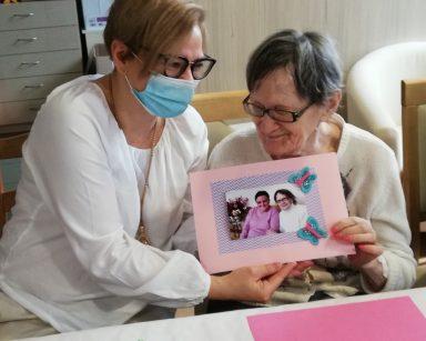Referentka Małgorzata Drochlińska i seniorka prezentują wspólnie udekorowane zdjęcie. Ma ramkę z różowego i fioletowego papieru z przyklejonymi niebieskimi motylkami.
