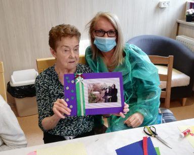 Kierownik Ilona Gajewska i seniorka prezentują wspólnie udekorowane zdjęcie. Ma ramkę z zielonego i fioletowego papieru z przyklejonymi kokardkami i kwiatkami.