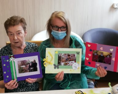 Kierownik Ilona Gajewska i seniorka prezentują wspólnie udekorowane zdjęcia. Pierwsze ma ramkę z zielonego i fioletowego papieru z przyklejonymi kokardkami i kwiatkami. Drugie zdjęcie ma ramkę z zielonego i żółtego papieru z przyklejonymi kokardkami serduszkami i kwiatkami. Na trzecim do czerwonego papieru przyklejone są serduszka i wstążki.