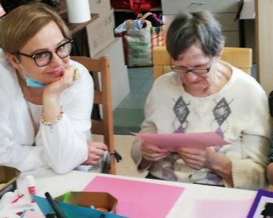 Referentka Małgorzata Drochlińska siedzi przy stole i się uśmiecha. Przy niej siedzi seniorka i ogląda zdjęcie naklejone na różowy arkusz papieru.