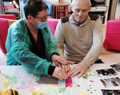 Kierownik Mariola Ludwicka i senior siedzą przy stole. Wspólnie pracują nad oprawieniem zdjęcia. Przed nimi na blacie widać rozłożone fotografie, papierowe ozdoby, nożyczki i klej.