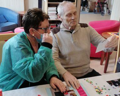 Kierownik Mariola Ludwicka i senior siedzą przy stole. Senior trzyma w dłoni zdjęcie, które będą dekorować. Przed nimi na blacie widać rozłożone fotografie, papierowe ozdoby, nożyczki i klej.