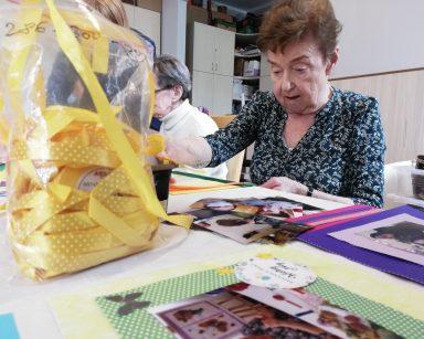 Przy stole siedzi seniorka. Przed nią na blacie widać żółta wstążkę do zdobienia zdjęć oraz rozłożone oprawione już fotografie. W tle widać inną seniorkę siedzącą przy stole.