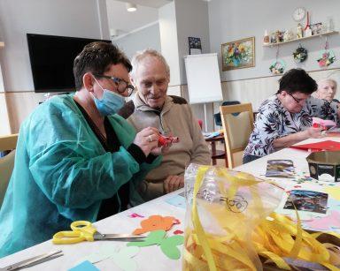 Kierownik Mariola Ludwicka i senior siedzą przy stole. Wspólnie pracują nad oprawieniem zdjęcia. Dalej widać dwie seniorki. One również ozdabiają zdjęcia. Przed nimi na blacie widać rozłożone fotografie, papierowe ozdoby, żółtą wstążkę, nożyczki i klej.