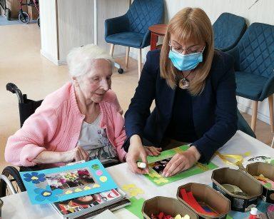 Dyrektor Agnieszka Cysewska i seniorka siedzą przy stole. Wspólnie pracują nad oprawieniem zdjęcia. Przed nimi na blacie oprawiona fotografię, papierowe ozdoby, nożyczki i klej.