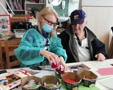 Kierownik Ilona Gajewska i senior siedzą przy stole. Wspólnie pracują nad oprawieniem zdjęcia. Przed nimi na blacie oprawiona fotografię, czerwoną wstążkę, papierowe ozdoby, nożyczki i klej.