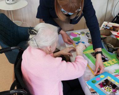 Dyrektor Agnieszka Cysewska i seniorką. Seniorka siedzi przy stole. Wspólnie pracują nad oprawieniem zdjęcia. Przed nimi na blacie oprawiona fotografia i papierowe ozdoby.