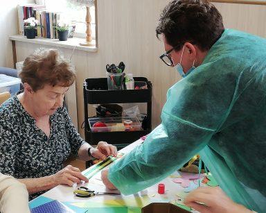Kierownik Mariola Ludwicka nachyla się nad stołem. Naprzeciwko siedzi seniorka i dekoruje swoje zdjęcie.
