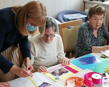 Dyrektor Agnieszka Cysewska i dwie seniorki pracują nad ozdobieniem zdjęć. Przed nimi na blacie rozłożone akcesoria do dekorowania