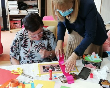 Dyrektor Agnieszka Cysewska i seniorka wspólnie ozdabiają zdjęcie w papierowej ramce
