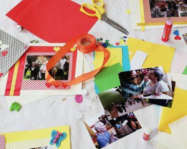 Na blacie rozłożone akcesoria i ozdoby do dekorowania zdjęć: nożyczki, kleje, wstążki, arkusze kolorowego papieru, motylki, serduszka.