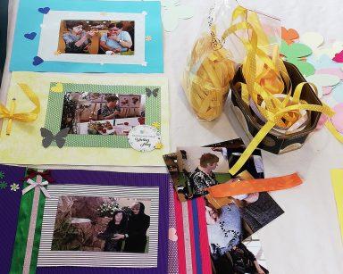 Na blacie trzy oprawione i ozdobione zdjęcia. Obok, wstążki, papierowe ozdoby, fotografie
