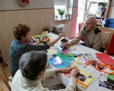 Troje seniorów siedzi przy stole. Pracują nad oprawieniem i ozdobieniem zdjęć.