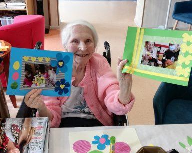 Seniorka prezentuje oprawione przez siebie zdjęcia. Ramki są udekorowane papierowymi motylami i serduszkami.