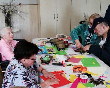 Kierownik Ilona Gajewska, senior i dwie seniorki pracują nad ozdobieniem zdjęć. Przed nimi na blacie rozłożone akcesoria do dekorowania.