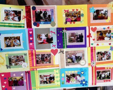 Na blacie leży 14 zdjęć. Wszystkie są oprawione w ozdobne ramki z kolorowego papieru. Każda ramka jest udekorowana wstążkami, kokardami, a także wyciętymi z papieru serduszkami, motylkami i kwiatami.