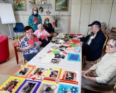 Przy stole dyrektor Agnieszka Cysewska, kierownik Ilona Gajewska i seniorzy. Na blacie rozłożone zdjęcia w ozdobnych ramkach.