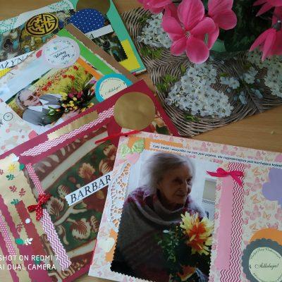 Na blacie zdjęcia seniorek naklejone na arkusze papieru i ozdobione papierowymi kolorowymi motylami, wstążkami i kwiatami.