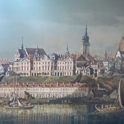 Obraz przedstawiający miasto nad rzeką.