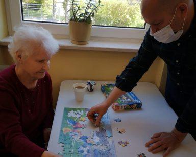 Seniorka i kierownik Arkadiusz Wanat wspólnie układają puzzle przy kawie.