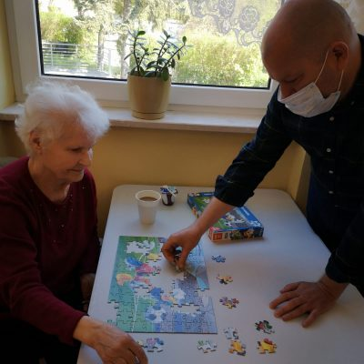 Seniorka i kierownik wspólnie układają puzzle przy kawie.