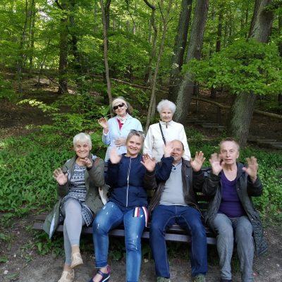 Terapeutka Beata Gadomska i seniorzy na ławce. Za nimi stoją dwie seniorki. Wszyscy machają. W tle drzewa z zielonymi liśćmi.