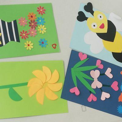 Kolorowe kartki. Na nich obrazki z papieru: wazon z kwiatami, kwiaty, serduszka, motyle, pszczółka.