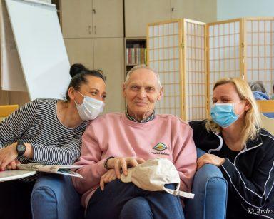 Jasny pokój. Terapeutka Magdalena Poraj-Górska, senior, neurologopedka Anna Szmaja-Wysocka siedzą obok siebie uśmiechnięci.