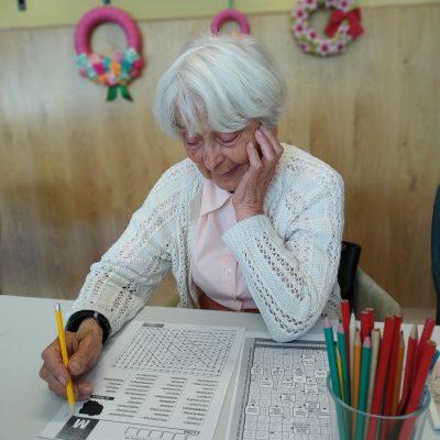 Seniorka siedzi przy stole i rozwiązuje wykreślankę. Obok gazeta z krzyżówką i kolorowe ołówki.