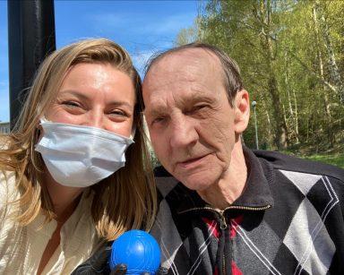 Słoneczny dzień, błękitne niebo. W tle las. Na pierwszym planie uśmiechnięci senior i psycholożka Maria Skubich-Wiczling.