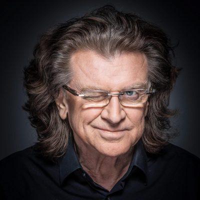 """Zdjęcie portretowe. Piosenkarz Zbigniew Wodecki uśmiecha się i """"puszcza oko""""."""