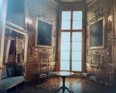 Fragment wnętrza Zamku Królewskiego. Wysokie okno. Bogato zdobione złote ściany na nich obrazy w złotych ramach.
