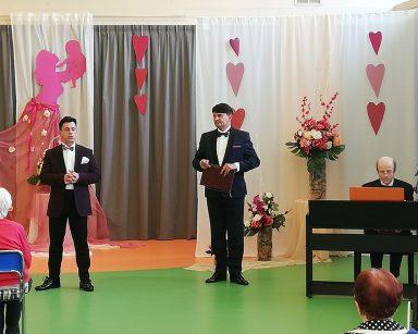 Dariusz Wójcik, Jacek Szymański i Michał Kaleta w trakcie koncertu dla seniorów. Za nimi dekoracja: serca, kwiaty.