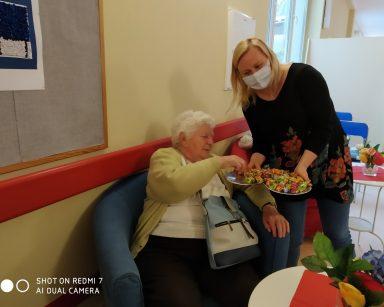 Neurologopedka Anna Szmaja-Wysocka pochyla się nad seniorką ze srebrną tacą pełną słodyczy. Seniorka częstuje się cukierkiem.