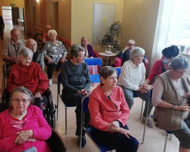 Seniorzy oraz pracownicy siedzą i czekają na koncert.