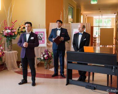 Dariusz Wójcik, Jacek Szymański i Michał Kaleta w trakcie koncertu dla seniorów. Za nimi dekoracje z kwiatów.