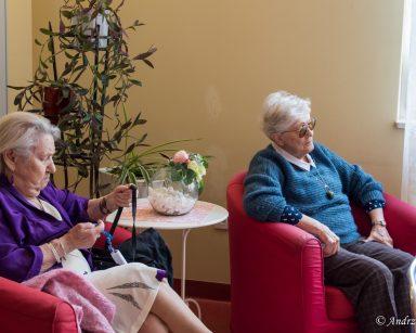 Seniorki siedzą w fotelach i słuchają koncertu.