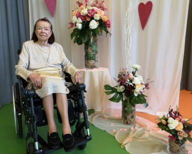 Uśmiechnięta seniorka. W tle dekoracja z papierowych serc i z kwiatów.