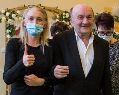 Uśmiechnięty senior i kierowniczka Ilona Gajewska trzymają się pod rękę. Idą na koncert.