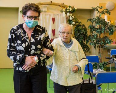 Seniorka trzyma kierowniczkę Mariolę Ludwicką pod rękę. Wspólnie idą na koncert.