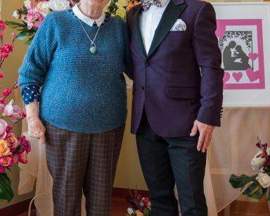 Uśmiechnięta seniorka i śpiewak Dariusz Wójcik pozują do wspólnego zdjęcia.