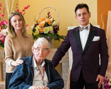 Senior pozuje do zdjęcia. Obok niego psycholożka Maria Skubich-Wiczling i śpiewak Dariusz Wójcik. W tle dekoracja z kwiatów.