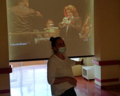 Terapeutka Magdalena Poraj-Górska wskazuje ręką ekran projektora. Na ekranie Zbigniew Wodecki gra na trąbce. Obok niego muzycy.