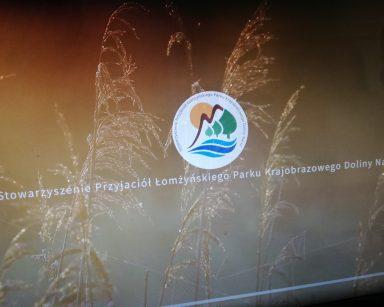 Ekran projektora. Na nim napis: Stowarzyszenie Łomżyńskiego Parku Krajobrazowego Doliny Narwi i logo.
