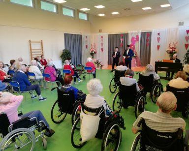 Sala udekorowana białym materiałem. Na nim różowe serca. Seniorzy i pracownicy siedzą. Przed nimi odświętnie ubrani muzycy.