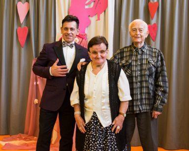 Śpiewak Dariusz Wójcik pozuje do zdjęcia z dwojgiem seniorów.