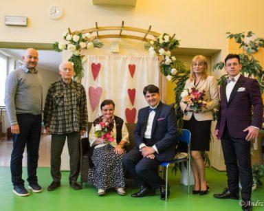 Muzycy, dyrektorka Agnieszka Cysewska, kierownik Arkadiusz Wanat pozują do zdjęć z seniorami. Za nimi dekoracje z kwiatów.